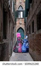 Venice Italy, February 2018. Two women in masks and ornate blue and pink costumes standing in front of an old blue door at the end of an alley in Venice during the carnival (Carnivale di Venezia).