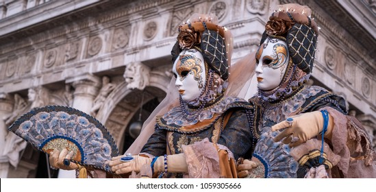 Venice Italy, February 2018. Two women in traditional costumes and masks, with decorated fans, standing in front of the arches at St Marks Square during the Venice Carnival