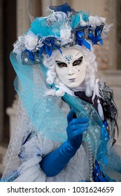 Venice Italy, February 2018. Woman holding fan and wearing colorful mask and hat, and ornate costume at the Doges Palace, San Marco, during Venice Carnival (Carnivale di Venezia)