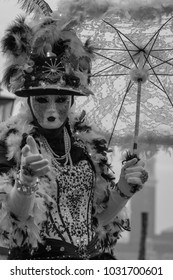 Venice Italy, February 2018. Woman holding parasol and wearing mask and ornate hat and costume standing with back to the Grand Canal during Venice Carnival. Photographed in monochrome.