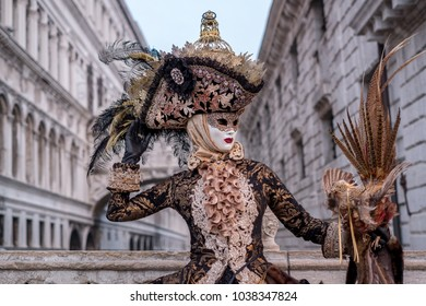 Venice Italy, February 2018. Woman in mask, dressed in black and gold costume, carrying birdcage, standing with the Bridge of Sighs in the background during the Venice Carnival (Carnivale di Venezia)