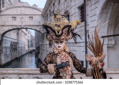 Venice Italy, February 2018. Woman in costume and mask, carrying feathered bird and birdcage, standing with the Bridge of Sighs in the background during the Venice Carnival (Carnivale di Venezia)