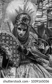Venice Italy, February 2018. Woman holding fan and wearing feathered mask and ornate costume standing against a wall of books during Venice Carnival / Carnivale di Venezia. Photographed in monochrome.