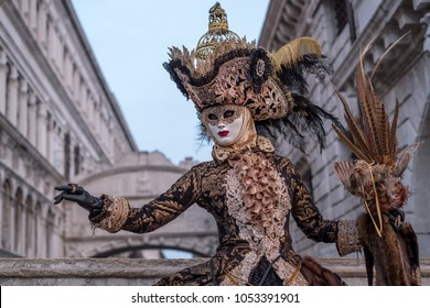 Venice Italy, February 2018. Woman in mask, dressed in black and gold costume, carrying birdcage, standing with the Bridge of Sighs in the background during the Venice Carnival (Carnival di Venezia)