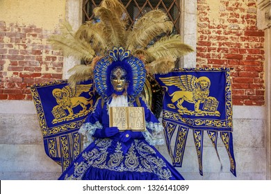 Venice, Italy - February 23 2019: Carnival mask and costume pose in Saint Mark square.Masked person in traditional costume pose at a Venetian square during the Venice 2019 Carnival.