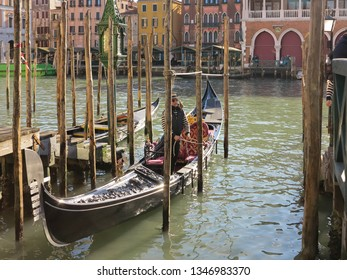 Venice, Italy - February 23 2019 - A gondolier gets ready to take his gondola out on the water.  Venice is famous for its gondoliers and gondolas, which are used for transport throughout the city.