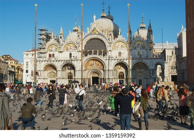 Venice, Italy - February 26, 2007: Tourists feed pigeons make photos with Saint Mark Basilica at the background at Piazza San Marco in Venice, Italy.