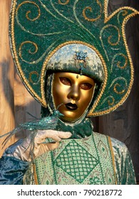 Venice, Italy - February 27 2006: portrait of a lady in green carnival costume with golden mask and green artificial bird on her hand