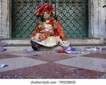 Venice, Italy - February 27 2006: woman with red and silver carnival costume and big hat of flowers sitting in front of a church door