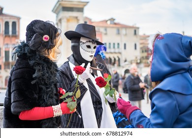 VENICE, ITALY - FEBRUARY 27, 2017: Disguised people during the Carnival of Venice. It is an annual festival that starts around two weeks before Ash Wednesday and ends on Shrove Tuesday or Mardi Gras