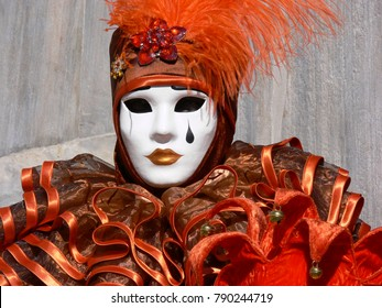 Venice, Italy - February 28 2006: woman with orange harlequin costume while carnival