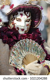 Venice, Italy - February 5, 2018: person in costume with Handmade carnival costume with a large fan in hand