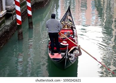 VENICE, ITALY - FEBUARY 11, 2018: Gondola with gondolier and tourists in Venice, Italy