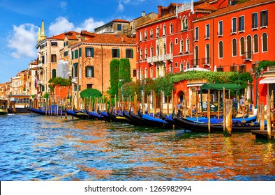 Venice, Italy. Gondolas with floating at piers by Grand Canal among antique buildings and traditional italian Venetian architecture. Sunny evening sunset with blue sky and clouds.