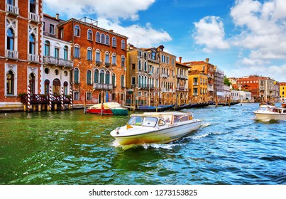 Venice, Italy. High-speed water motorboat floating by at Grand Canal vintage street among old italian houses with gondolas and by piers. Summer day blue sky clouds.