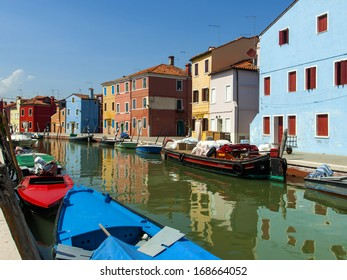 Venice, Italy, island of Burano in the Venetian lagoon, June 21, 2012. Colorful houses on the channel banks. The island attracts tourists unique coloring picturesque houses of local residents