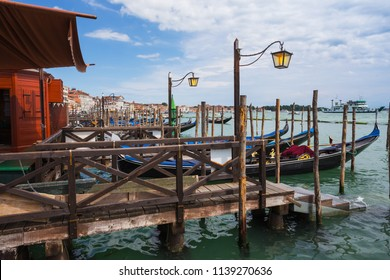 VENICE, ITALY - IUNE 26, 2014. Old gondola pier ashore Grand channel (Canal Grande). The grand channel is the main transport artery of Venice and its most known channel