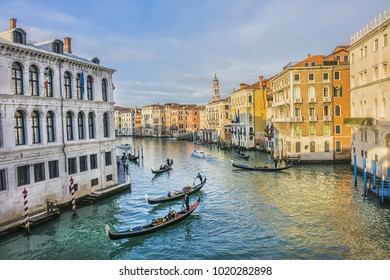 VENICE, ITALY - JANUARY 04, 2018: Gondoliers rowing a gondola with tourists on Grand Canal near Rialto Bridge. Gondola is the most popular tourist activity in Venice.