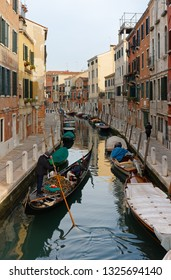 VENICE, Italy - January 12, 2019: A gondolier brings some tourists along a quiet canal in the Dorsoduro district