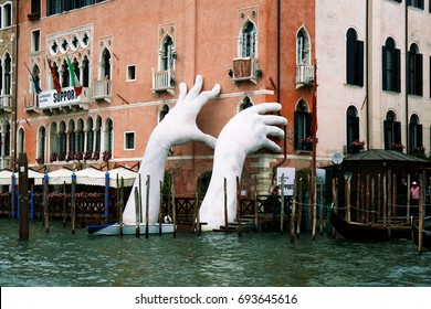 VENICE, ITALY - JULY 02, 2017: Support by Lorenzo Quinn. Gigantic hands rise from water to support the Ca' Sagredo Hotel, a statement of the impact of climate change and rising sea levels.