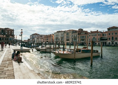 VENICE, ITALY - JULY 03, 2017: Tourists sit on the steps of Grand Canal. Venice is a popular tourist destination for its uniqueness, art and architecture.