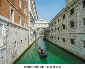 Venice / Italy - July 10, 2014: View of one of the canals of venice with old houses and a gondolier. Blue sea, summer day. Outdoor tourism in famous places.