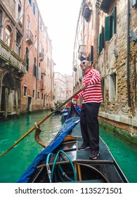 Venice / Italy - July 10, 2014: View of one of the canals of venice with old houses and a gondolier smiling. Blue sea, summer day. Outdoor tourism in famous places.