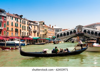 VENICE, ITALY - JULY 12: Tourists travelling on gondolas and boats on Grand Canal under Rialto Bridge on July 12, 2010 in Venice, Italy