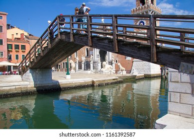 VENICE, ITALY - JULY 18 2014: a small wooden bridge over a canal in Venice