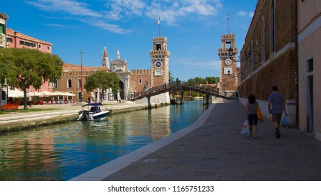 VENICE, ITALY - JULY 18 2014: a shaded walkway next to a canal
