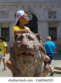 VENICE, ITALY: JULY 18 2014: one of the popular poses in Venice is sitting on this lion