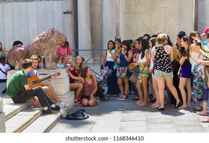VENICE, ITALY: JULY 18 2014: a group of girls gathered around two guys with a guitar