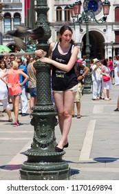 VENICE, ITALY: JULY 18 2014: a young woman hanging on a lamp post in Saint Mark's Square
