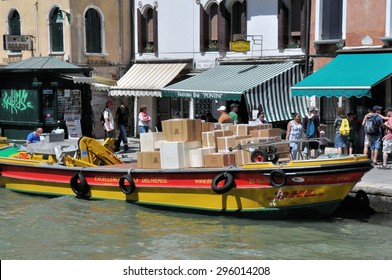 VENICE, ITALY - JULY 18: DHL delivery boat with packages in canal on July 18, 2012 in Venice. Delivery barges are the most common kind of utility vehicle in Venice.