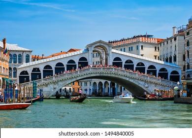 VENICE, ITALY - JULY 19, 2019: Rialto bridge with boats and gondolas passing under on Grand Canal, Venice, Italy
