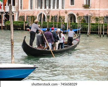 Venice, Italy - July 25, 2011: Two gondoliers row a traditional traghetto gondola across the Grand Canal near the Rialto Bridge as passengers stand. One of seven such routes across the canal.