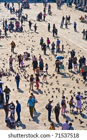 VENICE, ITALY - JULY 4: Tourists on San Marco square feed large flock of pigeons on July 04, 2007 in Venice. San Marco square is the largest and most famous square in Venice.