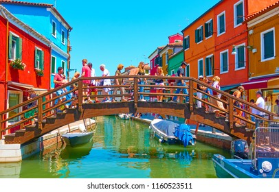 Venice, Italy - June 16, 2018: Lots tourists on the bridge over canal in Burano island in Venice
