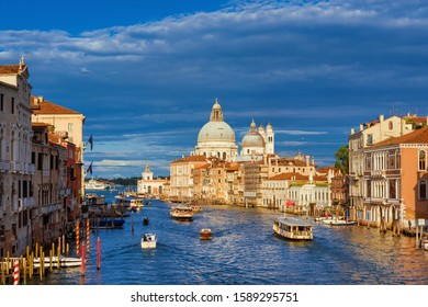 VENICE, ITALY - JUNE 17, 2016: Public transport and tourism in Venice. Gondolas, ferry, water bus and taxi cross the Grand Canal near the iconic Salute Basilica