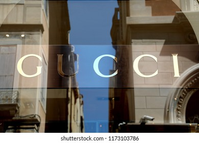 VENICE, ITALY - JUNE 18, 2018: striking Gucci signage in Venice main street with buildings reflections