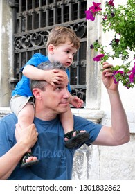 Venice / Italy - June 19 2016 - Dad carries toddler boy on shoulders on street in Venice Italy, and they stop to smell red roses on wall.