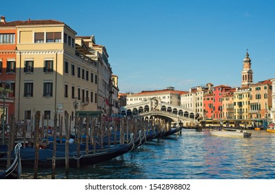 VENICE, ITALY - JUNE 2, 2019: A row of docked gondolas resting at their mooring sites just before the Rialto bridge in Venice, Italy