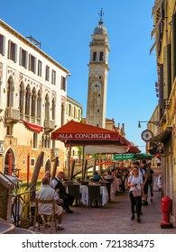 Venice, Italy - June 20, 2017: Falling campanile over a Venetian Canal in Venice, Italy. Unrecognizable people are walking down the street in the old center.