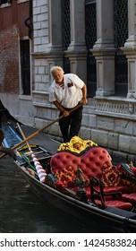 Venice, Italy -June 20, 2018: A gondolier steering his gondola in Venice - Image
