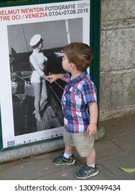 Venice / Italy - June 23 2016: Little boy on Venice Italy street looking at Helmut Newton poster of 1950s bombshell.
