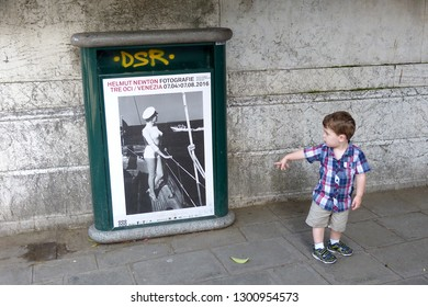 Venice / Italy - June 23 2016: Curious little boy on street of Venice Italy wearing checkered shirt and shorts stops to point and stare at vintage 1950s Helmut Newton poster with posing sexpot.