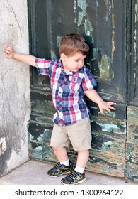 Venice / Italy - June 23 2016: Little boy in checkered red and blue shirt and khaki shorts standing in front of weathered old door in Venice, Italy.