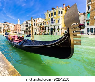VENICE, ITALY - JUNE 26, 2014: Tourists travel on gondolas at canal Venice, Italy . Gondola trip is the most popular touristic activity in Venice.