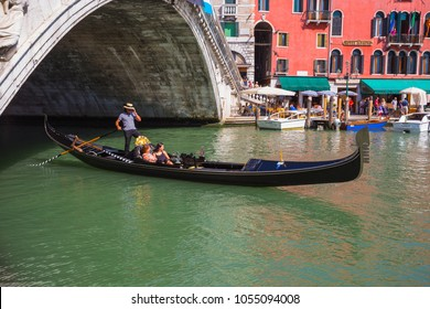 VENICE, ITALY - JUNE 26: Tourists travel on gondolas at canal on June 26, 2014 in Venice, Italy . Gondola trip is the most popular touristic activity in Venice.