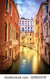 VENICE, ITALY - JUNE 28, 2015: Amazing narrow canal in Venice in the evening with antique bridge in the background, Italy